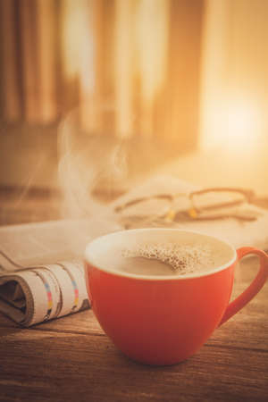 A cup of coffee and a  newspaper of coffee on a wooden table 版權商用圖片