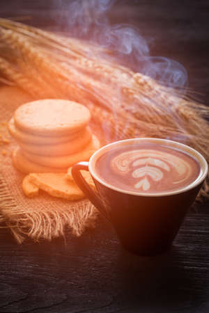 Hot coffee with late art and biscuits