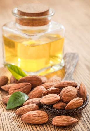 Bottle almond oil and almond on wood background 스톡 콘텐츠