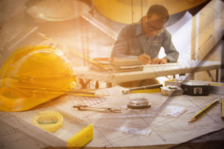 Architect man working with blueprints  in workplace for architectural plan,sketching a construction project