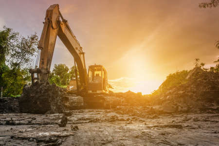 Backhoe with raised bucket at sunset