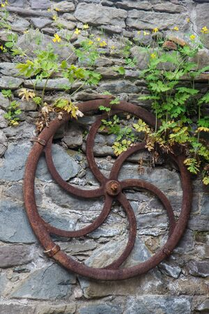 ranch background: Garden decoration with old and weathered wooden cart wheel