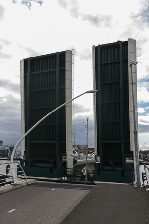 zaan: Open drawbridge, cargo ship, Zaanse Schans, Netherlands. Industrial boat, raised lifting bridge. Dutch architecture. Barge passing thru drawbridge over Zaan river, Holland. Editorial