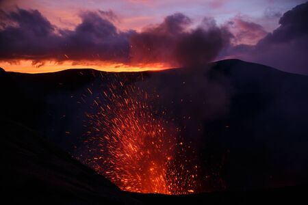 Eruption Yasur vulcano and sunset on the crater edge, Tanna, Vanuatu Stock Photo