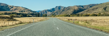 Mountain landscape with road and blue sky, Otago, New Zealand Stock Photo