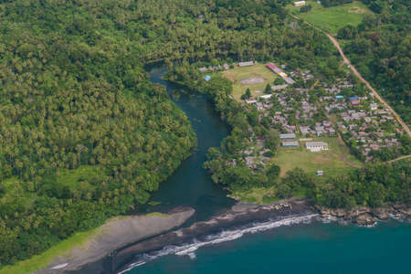 The tropical bay with stony beach, boats and buildings, aerial view. Luganville, Espiritu Santo, Vanuatu.