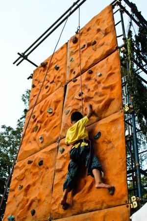 Thai boy climbing on a climbing wall