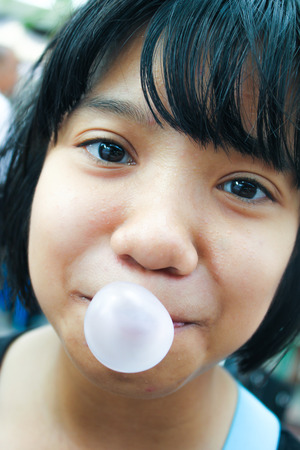 asian kid blowing a bubble gum in her mouth