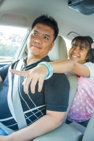 asian kid and her father in car photo