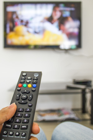 channel surfing with remote control in hand 写真素材