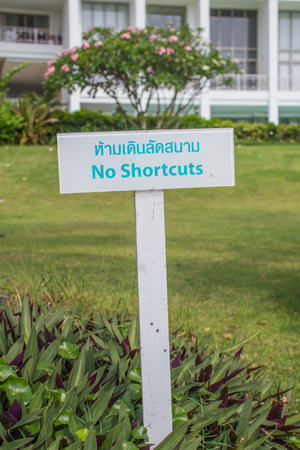 dont walk: warning sign dont walk on grass both English and Thai language in Thailand Stock Photo