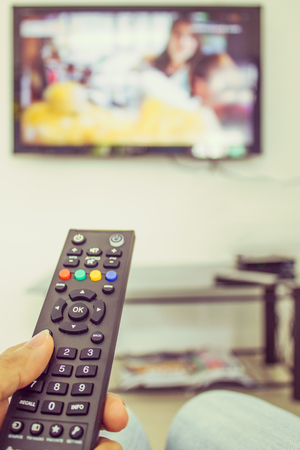 channel surfing: channel surfing with remote control in hand Stock Photo