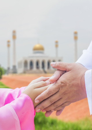 muslim child greeting her father on blur background of masjid Imagens