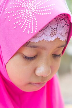 petite fille musulmane: petite fille musulmane dans jab salut rose lisant un livre