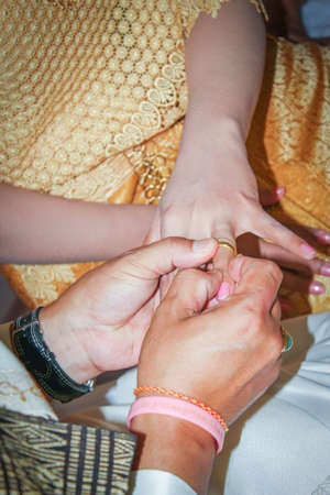 fingers put together: Thai groom put the wedding ring into bride hand