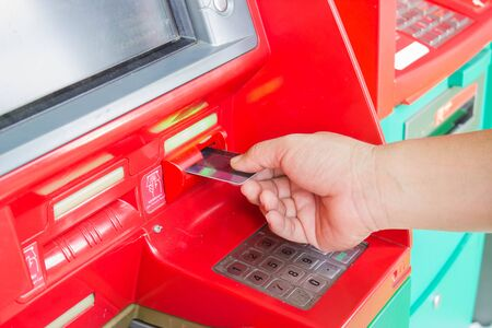 technology transaction: male hand  inserts credit card into the ATM to deposit money