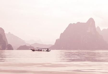thani: tourist in boat at Ratchaprapa Dam (Chaew Lan Dam) Surat Thani, Thailand photo in pink filter Stock Photo