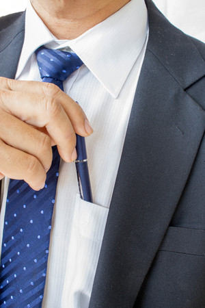 blue pen: business man pulling or putting blue pen in his pocket