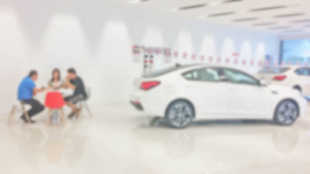 blur photo of car showroom with salesman and customers Stock Photo