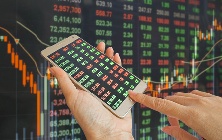 hand using mobile phone with background of stock market price