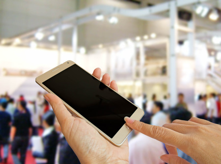 exhibition crowd: hand holding smart phone on blur photo of people at motorshow background