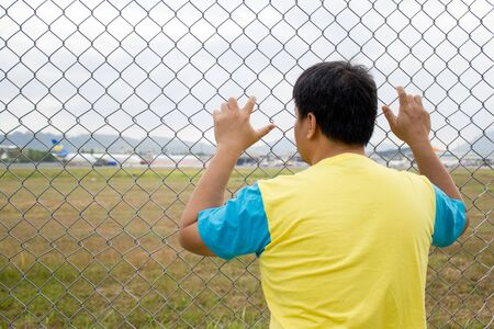 chain link: man hand holding on chain link fence at the airport, sad for someone leaving