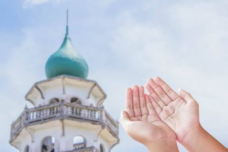 Human open empty hands with palms up over blurred public mosque background Stock Photo