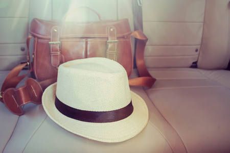 car accessory: vintage leather bag and hat in luxury car with sun light Stock Photo