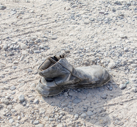 dirty feet: one old and dirty  boots on the rural road Stock Photo