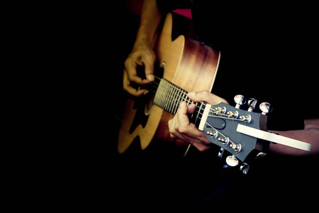Close up fingers of man playing acoustic guitar in retro filter