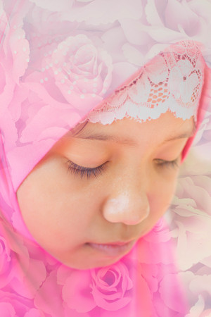 jab: double exposure of little muslim girl in pink hi jab and rose Stock Photo