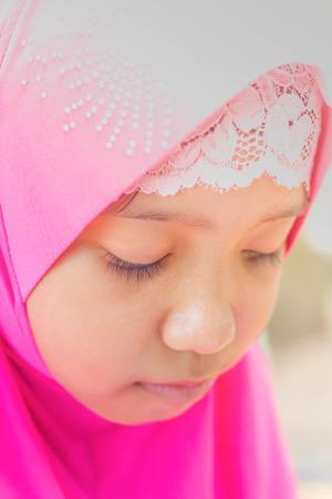 jab: little muslim girl in pink hi jab reading a book Stock Photo