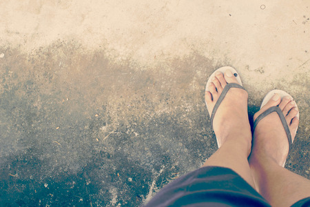 foot with old sandals on grungy floor in retro filter Stock Photo