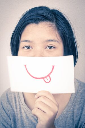 fake smile: girl smiling with mouth drawn on white paper Stock Photo