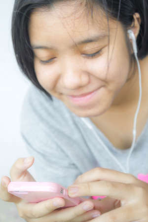 ear phone: Asian young girl listening to music from smartphone with ear phone