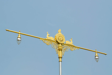 thai stretch: Golden statue of native thai art with street lamps on blue sky background