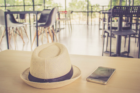 tabel: hat and smart phone on coffee shop tabel Stock Photo