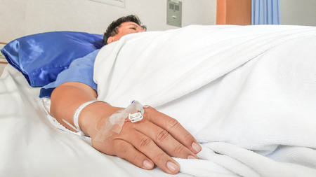 saline solution: close up of saline solution preparation on hand of man patient lying on the hospital bed