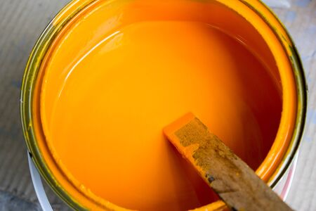 wood stick: abstract orange paint color in bucket with wood stick