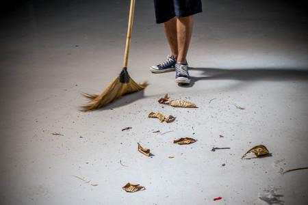hombre adolescente asiático barriendo las hojas secas en el suelo con la escoba carácter local