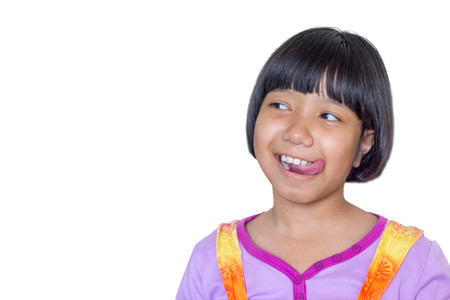 Asian Thai girl child shows delicious expression with tongue out