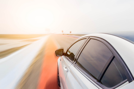 white new car on the highway road with sun light : concept photo of hope or moving forward