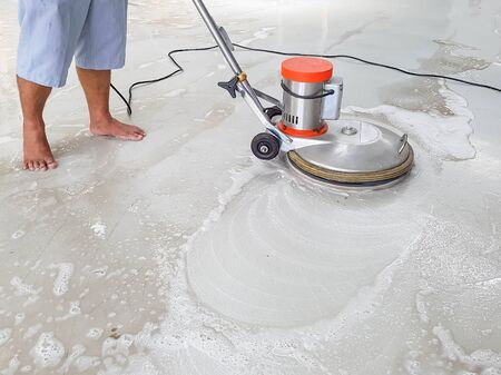 foots: worker using scrubber machine for cleaning and polishing floor in bare foots