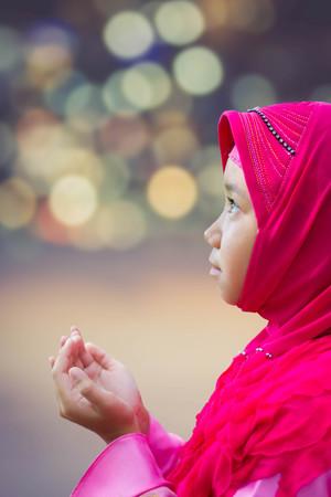 petite fille musulmane: petite fille d'enfant musulman asiatique en hijab rose (scraft musulmane) priant isolé sur floue bokeh
