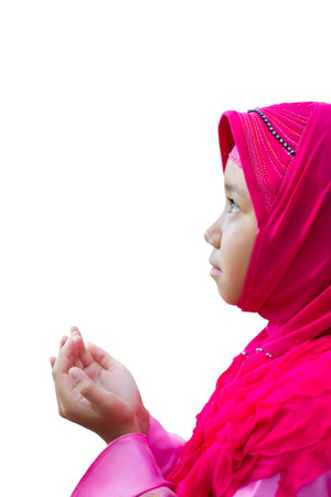 petite fille musulmane: little Asian Muslim kid girl in pink hijab (Muslim scraft) praying on nature bokeh background with soft sunlight Banque d'images