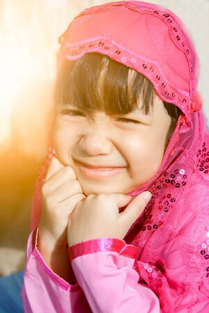 petite fille musulmane: little muslim girl in pink Hijab (scarf) and  smile