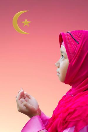 little Asian Muslim kid girl in pink hijab (Muslim scraft) praying on abstract background