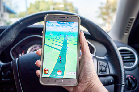 Songkhla, Thailand - 10 Aug 2016 :  Pokemon GO augmented reality smartphone game dangerous trend to catch pokemons while driving car Editorial