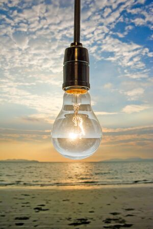 chandelier background: close up of vintage light bulb on background of sunset beach : concept photo of light Stock Photo