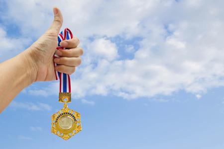 hand hold gold medal on blue sky background